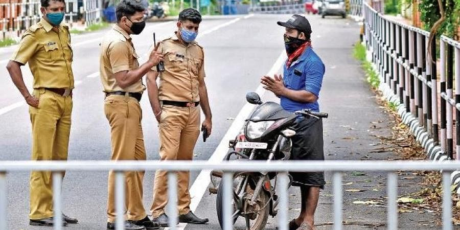 A motorist pleading to the police not to fine him for riding his bike without a valid reason during the triple lockdown. A scene from Vetturoad near  Kazhakootam, Thiruvananthapuram.