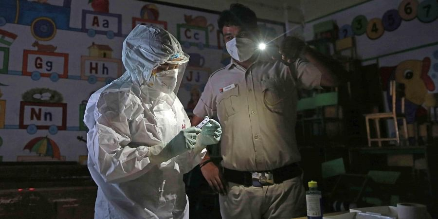With no electricity, a medical worker in PPE is assisted by a policemen while conducting Covid tests