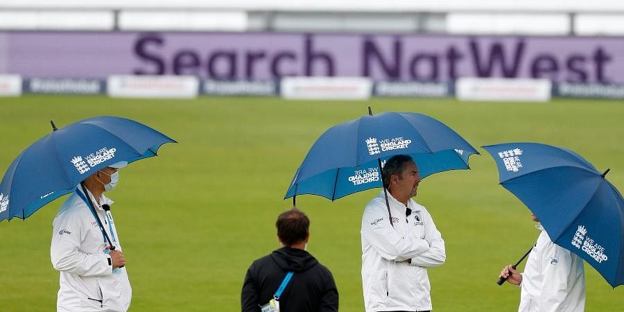 Umpires hold umbrellas as rain delayed start of the first day of the Test match between England and West Indies.