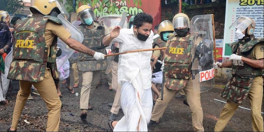 Police lathicharging a Yuva Morcha activist during a protest march to the Kozhikode collectorate demanding the resignation of Chief Minister Pinarayi Vijayan
