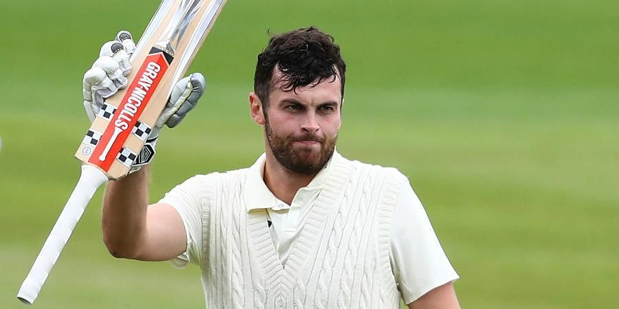 England's Dom Sibley raises his bat to celebrate scoring a century during the second day of the second cricket Test match between England and West Indies at Old Trafford in Manchester.