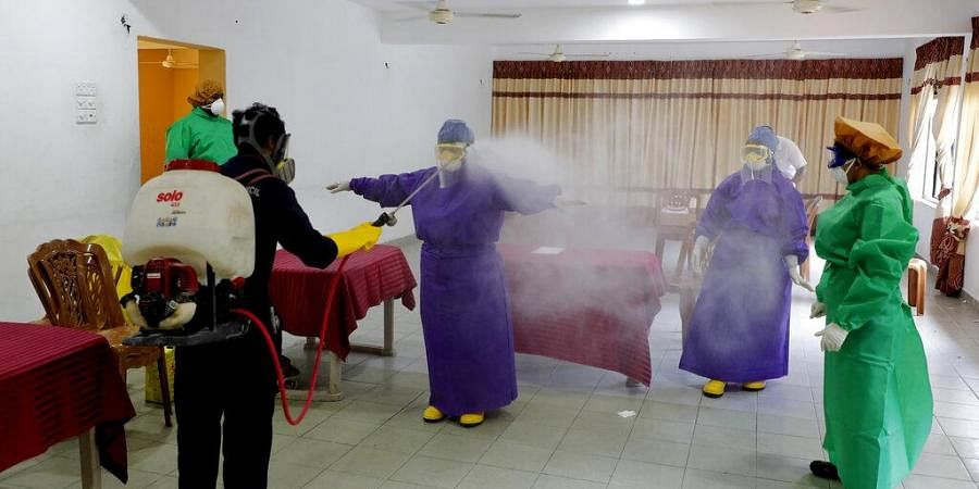 Sri Lankan municipal health workers are disinfected after a swab sample collecting session to test for COVID-19 in Colombo, Sri Lanka, Tuesday, July 14, 2020. (Photo | AP)