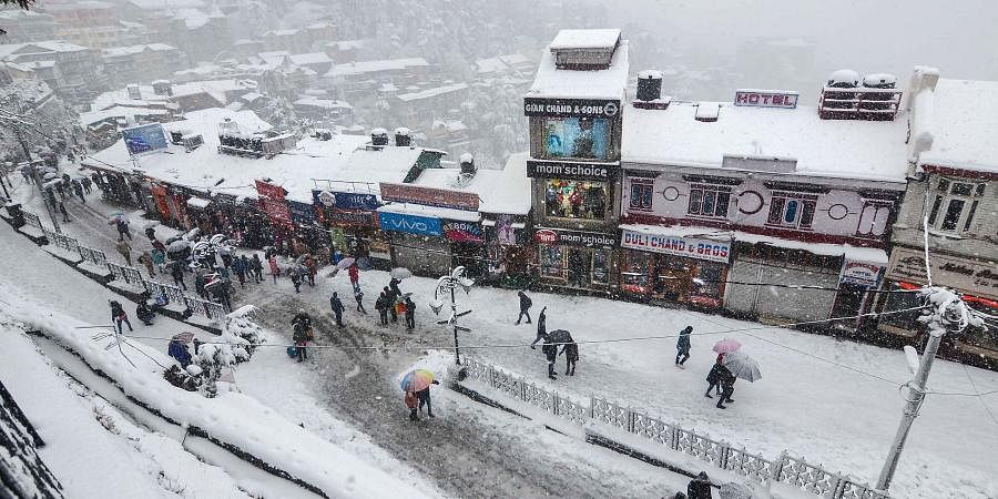 People walk on snow covered roads amid heavy snowfall in Shimla on Wednesday Jan. 8 2020. (Photo | PTI)