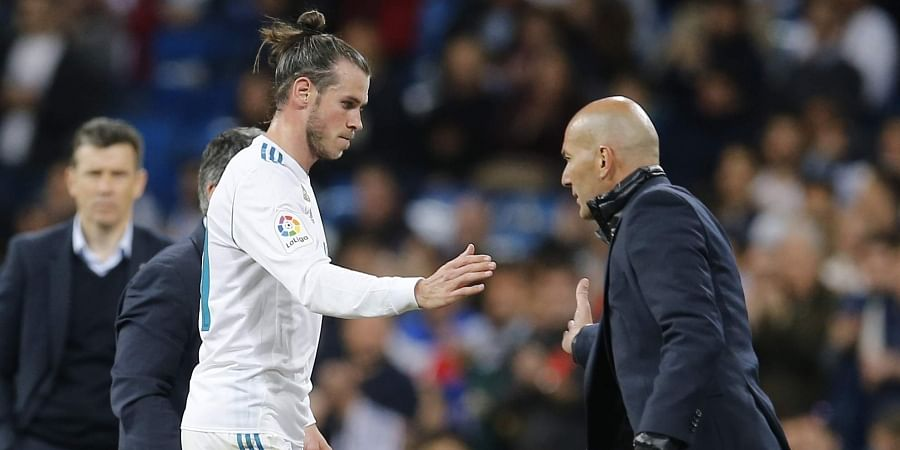 Real Madrid's Gareth Bale. left, shakes hands with Real Madrid's head coach Zinedine Zidane.