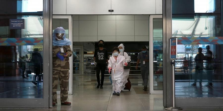 Passengers wearing PPE ket arrive at the Indira Gandhi International airport during the first day of resuming of domestic flights after the government imposed a nationwide lockdown as a preventive measure against the spread of the COVID-19 coronavirus in New Delhi on Monday.