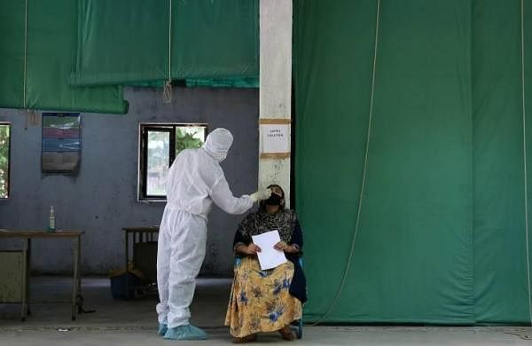 A health worker in PPE coveralls conducts a Covid-19 test at a Government school in New Delhi on Wednesday. (Photo | Shekhar Yadav, EPS)