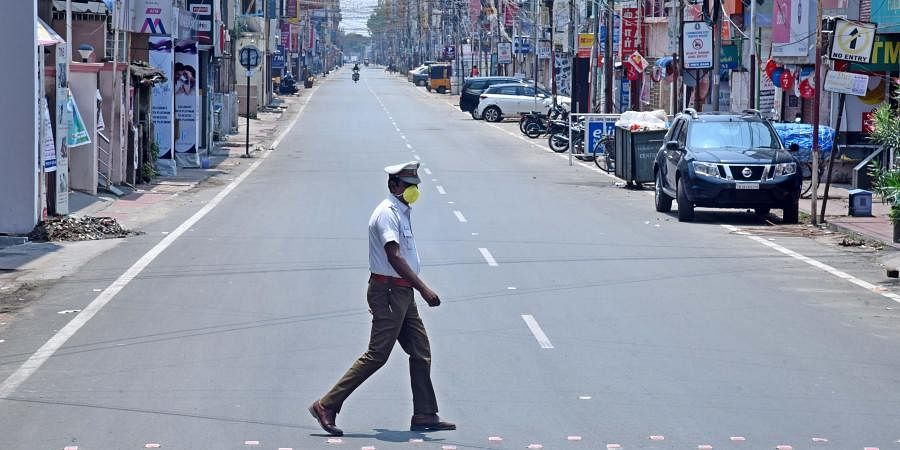 Traffic police person with a face mask seen on duty at the deserted oppanakara street in coimbatore on sunday following the janata curfew.