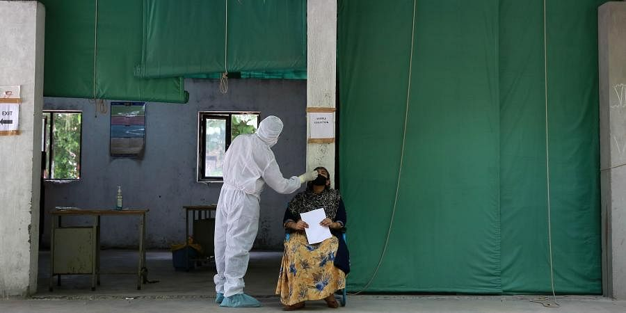 A health worker collects a swab sample for Covid-19 rapid testing at a government school.