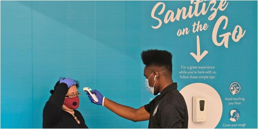 Bigard Ogbonna, right, checks a customer's temperature before they enter a store at the Garden State Plaza mall in Paramus, N.J., as New Jersey's indoor shopping malls reopened from their COVID-19 pause.