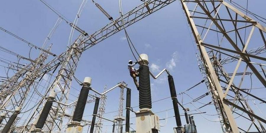 A technician repairs power supply lines at a power plant of Adani Power. (File photo | Reuters)