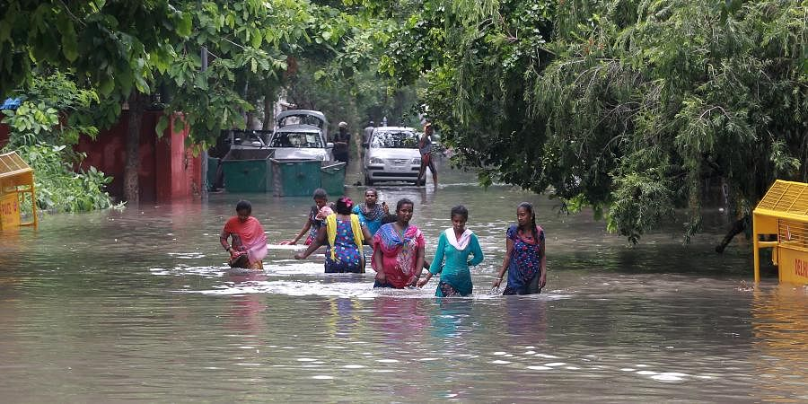 People wade on a flooded road following rains in New Delhi
