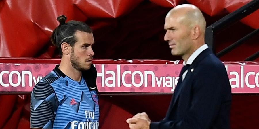 Real Madrid head coach Zinedine Zidane (R) talks with striker Gareth Bale during the Spanish La Liga soccer match.