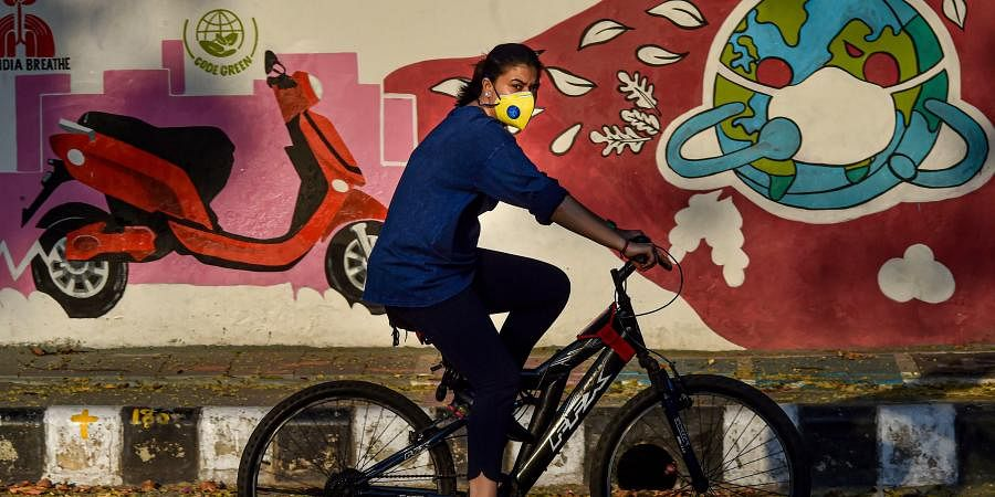 A woman cycles past a wall graffiti during the COVID-19 lockdown in New Delhi.
