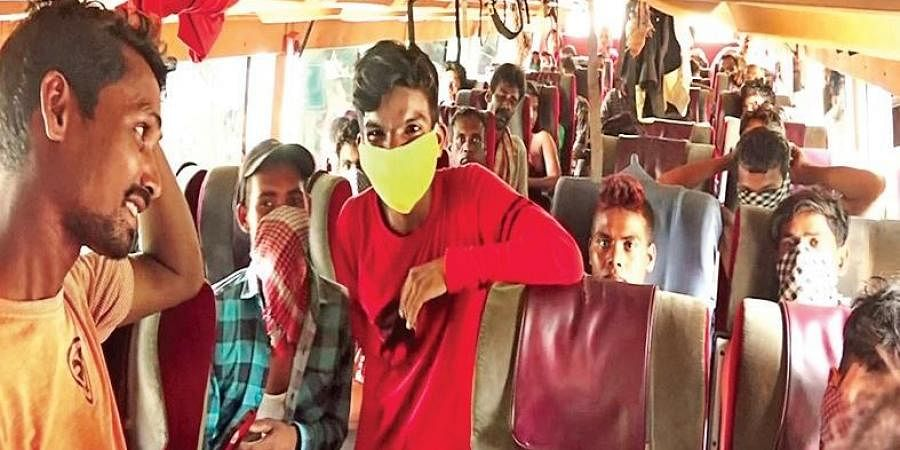 Migrant workers aboard a bus to Chennai at Khallikote in Ganjam district