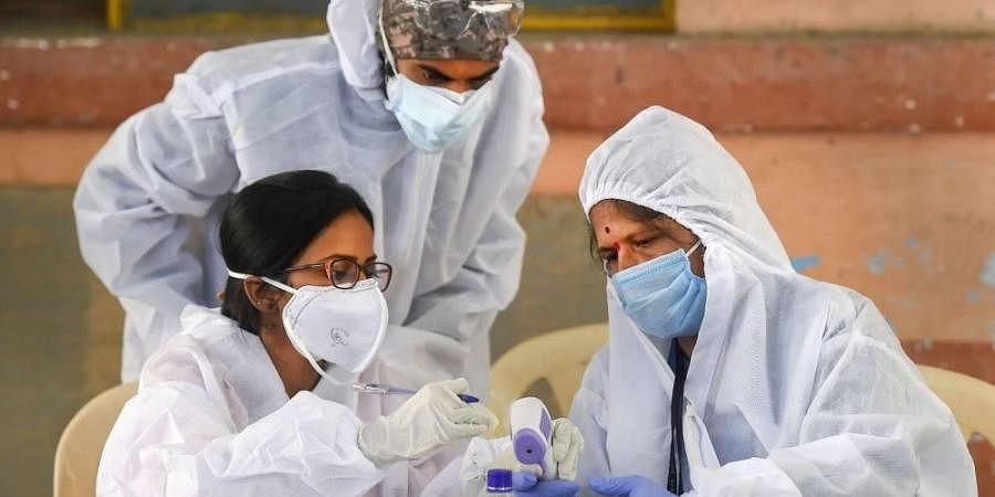Medical volunteers wearing protective gear check a thermometer gun scanner at a COVID-19 testing camp at Dadar in Mumbai Monday July 20 2020.