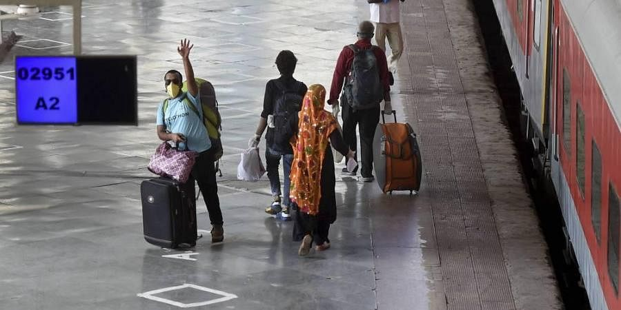 People with their luggage walk to board a special train for New Delhi after resumption of passenger train services by the Indian Railways in graded manner amid ongoing COVID-19 lockdown at Mumbai Central Railway Station