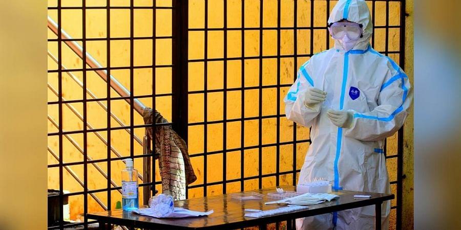 A health worker conducts a rapid antigen test in Bengaluru