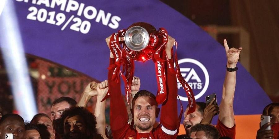 Liverpool's English midfielder Jordan Henderson (C) lifts the Premier League trophy with his team-mates. (Photo   AFP)