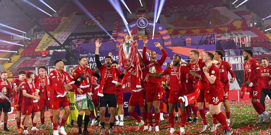 Liverpool players celebrate with the English Premier League trophy following the English Premier League soccer match between Liverpool and Chelsea at Anfield Stadium in Liverpool, England. (Photo |AP)