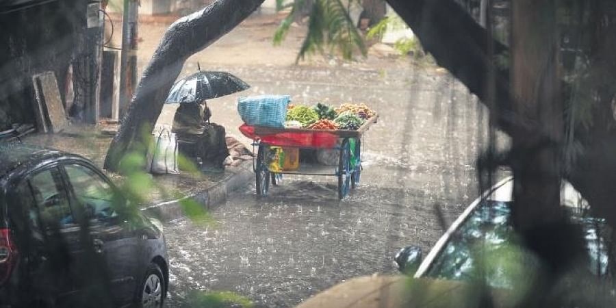 Woman street vendor takes shelter under a umbrella from a sudden downpour during lockdown