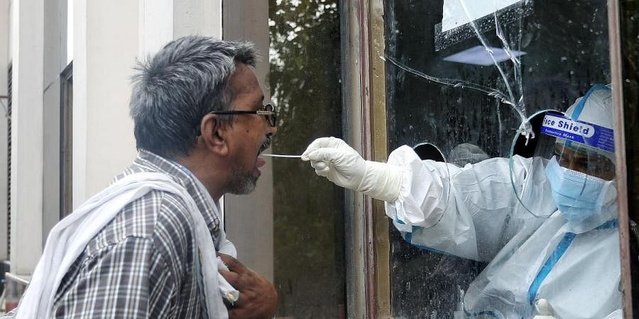 A health worker collects swab samples from a man at the COVID-19 testing center in New Delhi on Friday