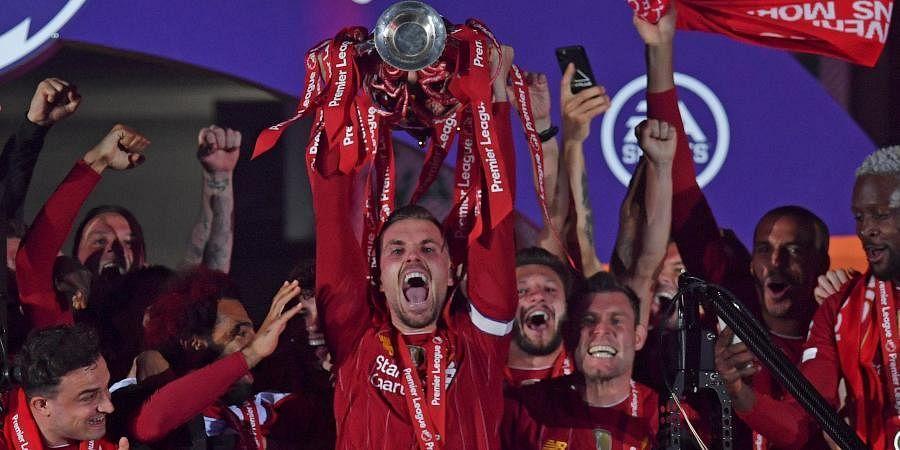 Liverpool's Jordan Henderson holds the English Premier League trophy aloft.