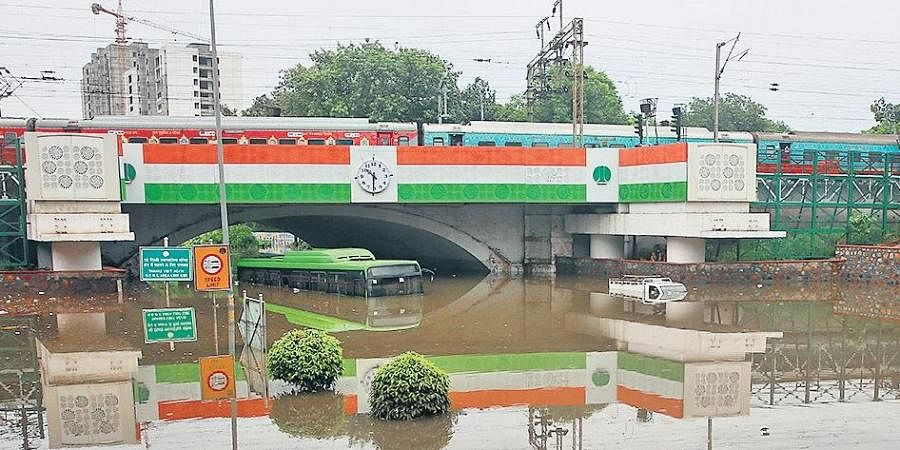 A DTC bus and a good carrier can been seem submerged under the Minto Road Railway Bridge after heavy rains.