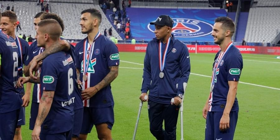 Paris Saint-Germain's French forward Kylian Mbappe (C) walks with crutches after winning the the French Cup final football match. (Photo | AFP)