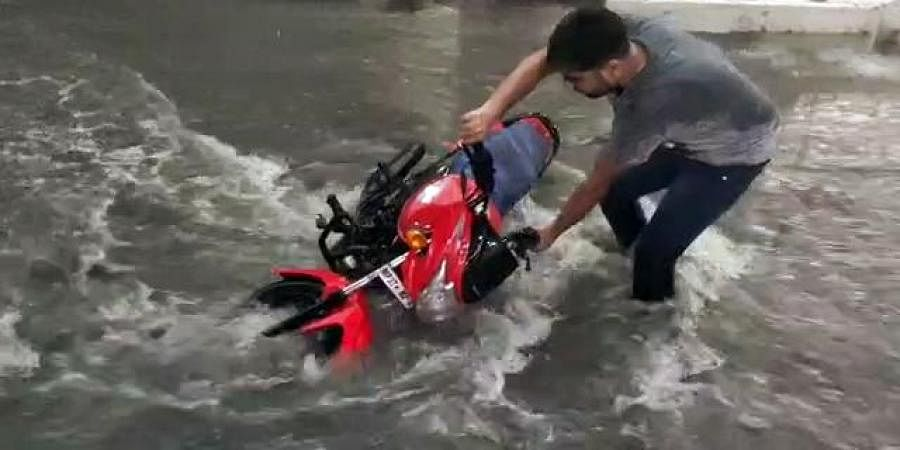 A man trying to save two-wheeler as heavy rainfall triggered flash floods in parts of Sehore