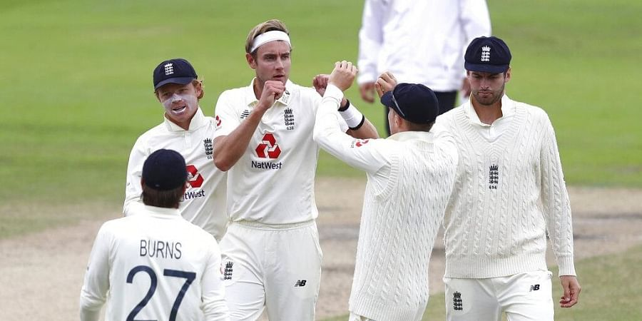 England's Stuart Broad, center, celebrates with teammates the dismissal of West Indies' Kemar Roach.