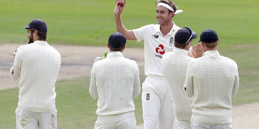 England's Stuart Broad, center, holds the ball to celebrate taking 500 wickets during the fifth day of the third cricket Test match between England and West Indies.