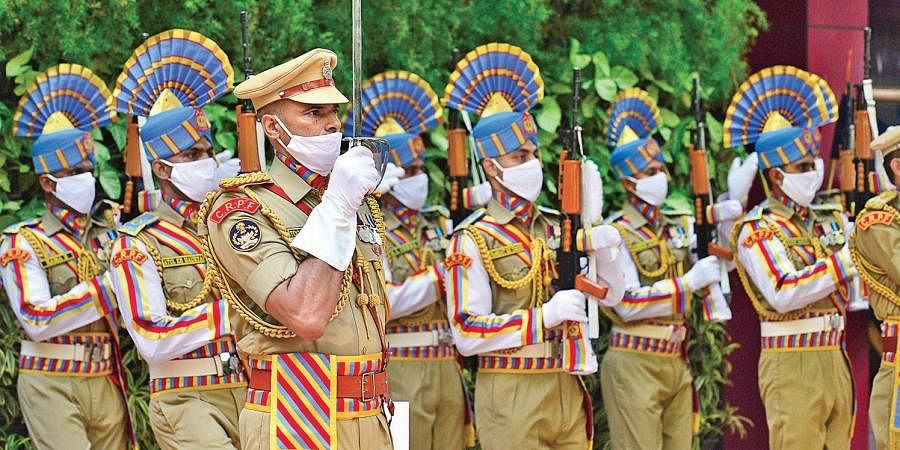 CRPF personnel wearing masks attend a function on the occasion of the 82nd Raising Day of the force in New Delhi on Monday