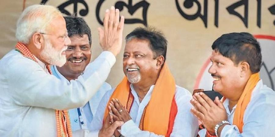 Both Mukul Roy (C) & Arjun Singh are circumspect about BJP's poll prospects in Bengal.