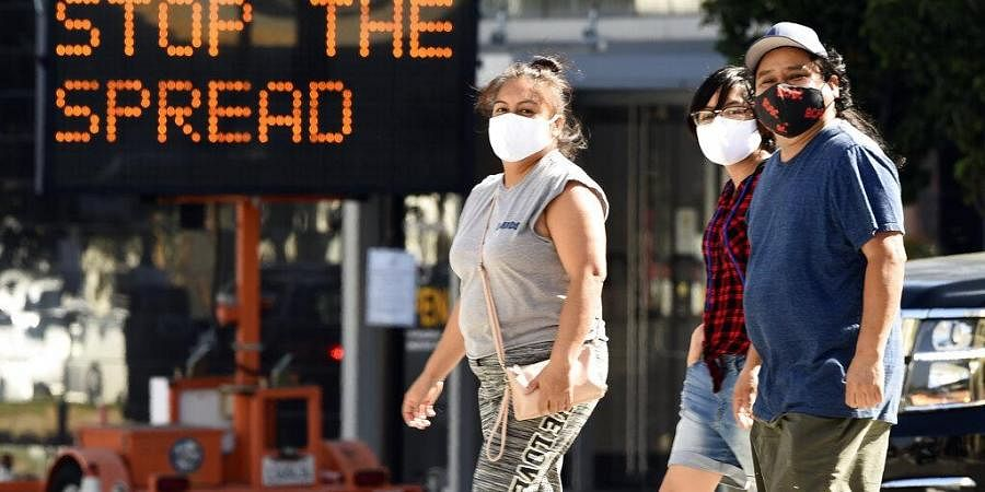 Pedestrians wear masks as they walk in front of a sign reminding the public to take steps to stop the spread of coronavirus. (Photo | AP)