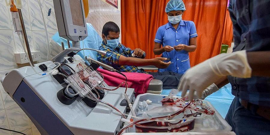 A COVID-19 survivor donates plasma at a Plasma Bank