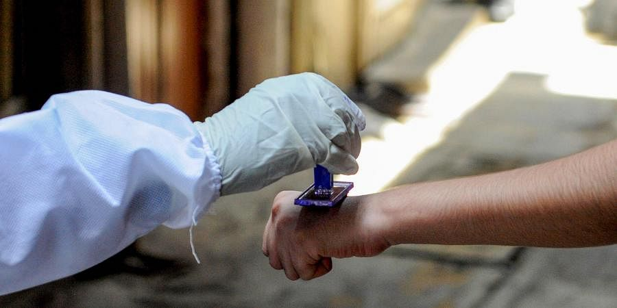 A health worker marks the hands of residents with home quarantine stamp at Bhaji Galli Road no. 3 of Andheri East in Mumbai Saturday June 27 2020.