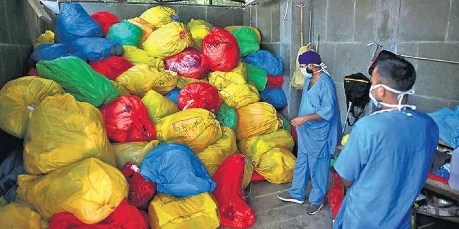 Staff members dispose of PPE kit waste in LNJP Hospital.