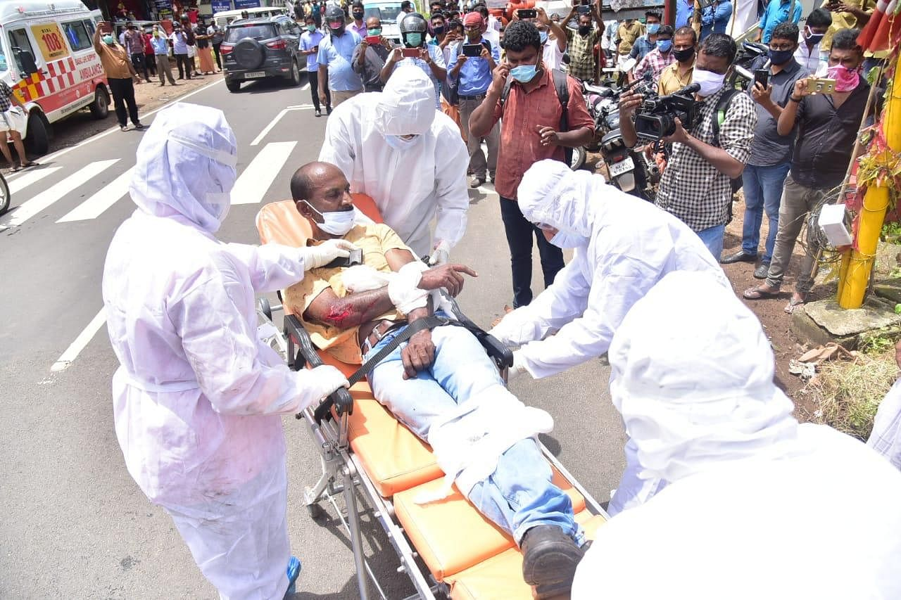 The man is laid on the stretcher, completely strapped in, and is unable to move, but is still seen to be agitated.