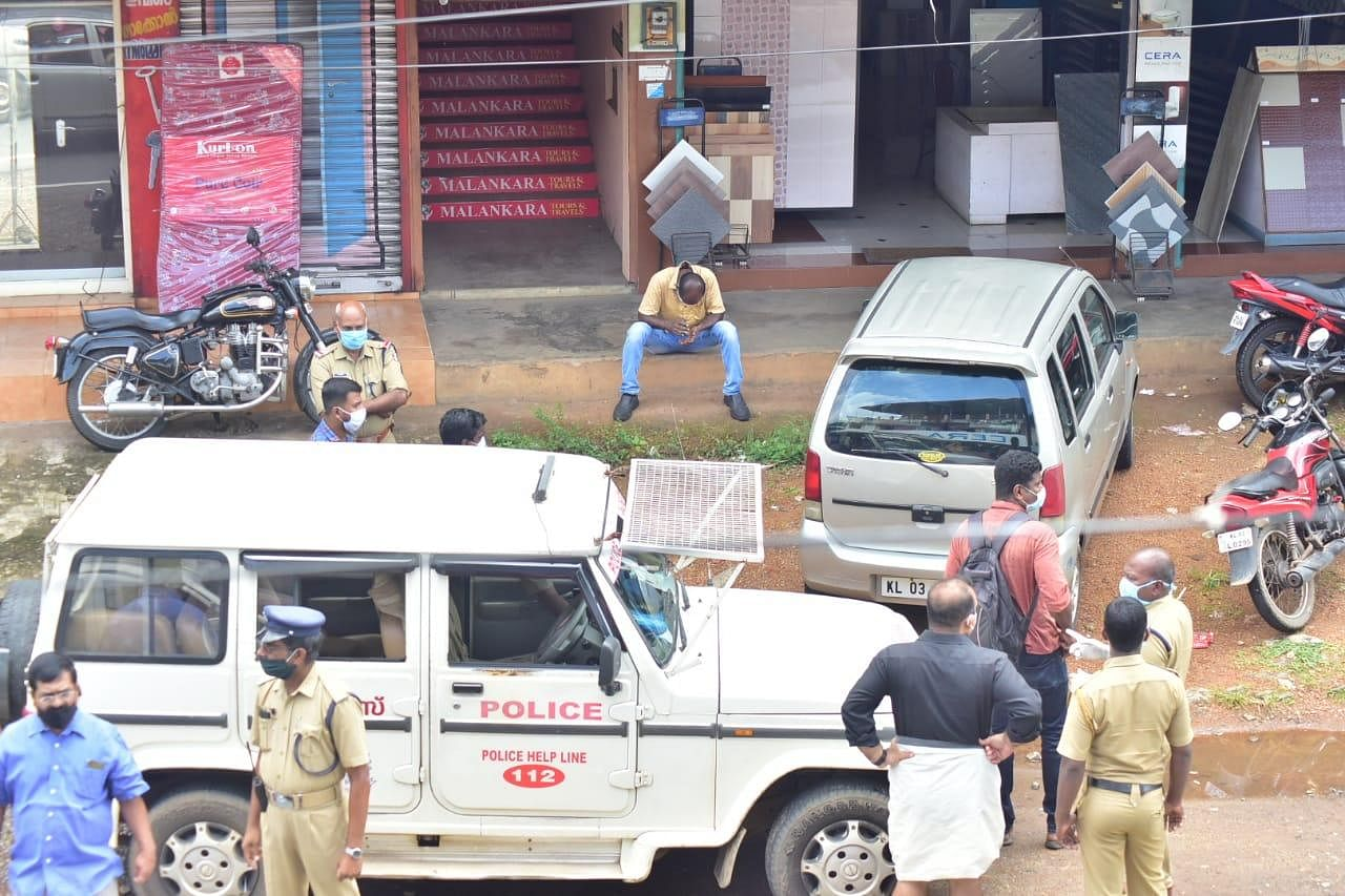 A man who returned from Riyadh on July 3rd is seen sitting on the step of a shop in Pathanamthitta surrounded by police officers who've arrived to take him for violating quarantine rules of the state.