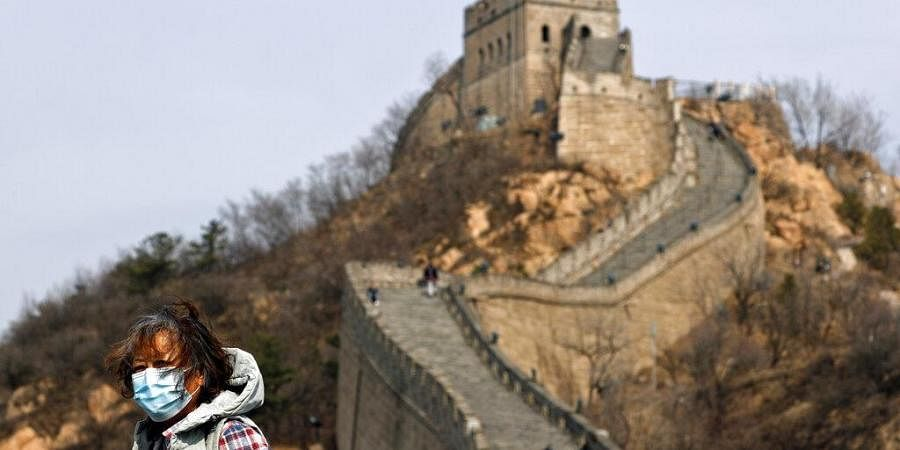 A woman wearing a protective face mask visits the Badaling Great Wall of China after it reopened in China. (Photo | AP)