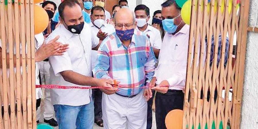 Rajdhani College principal Rajesh Giri inaugurates a solar plant.