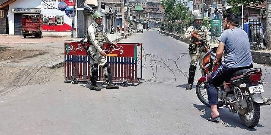 Security forces stop people during restrictions imposed in Srinagar.   Zahoor Punjabi