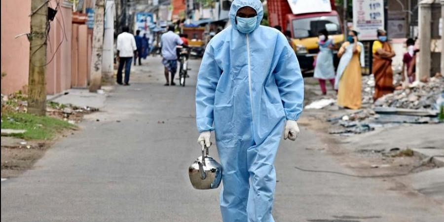 An employee of Chennai corporation going in the streets of Porur with a kettle filled with Kabasurakudineer' to serve to the residents at their doorstep to prevent coronavirus.