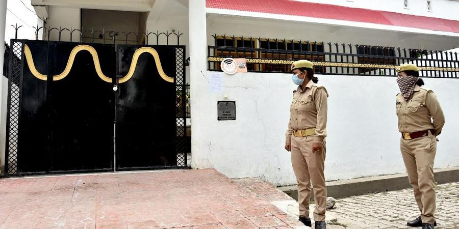Police personnel stand guard outside the residence of gangster Vikas Dubey at Krishna Nagar in Lucknow on Thursday