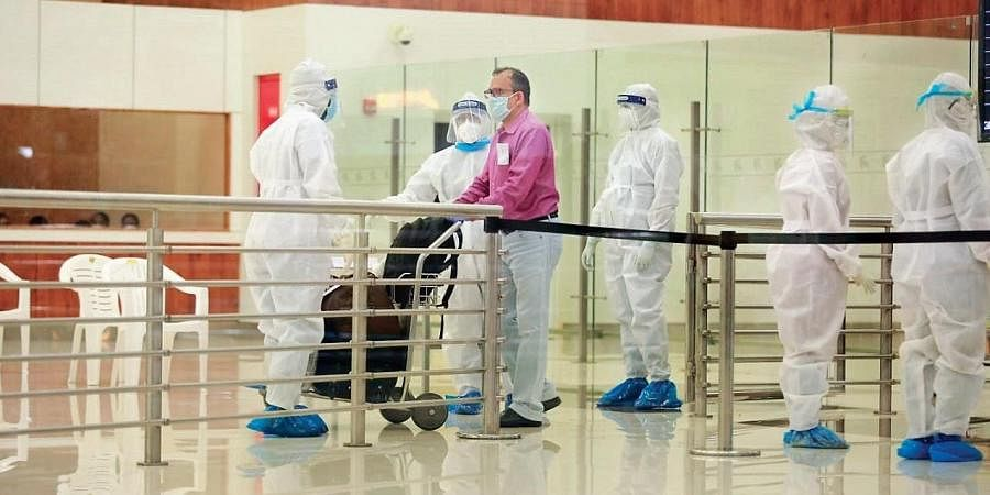 An expatriate who arrived from Abu Dhabi on an evacuation flight comes out of the Kochi airport on Thursday