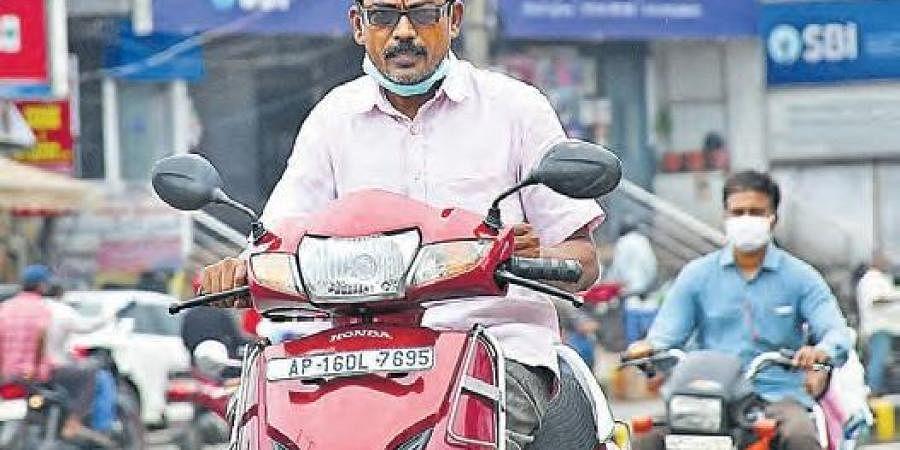 A man drives scooter without wearing a mask in Vijayawada I PRASANT MADUGULA