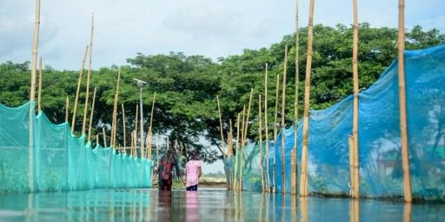 Children make their way through floodwaters on the outskirts of Dhaka on July 30, 2020.
