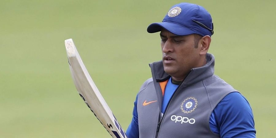 India's MS Dhoni, second right, carries his bats before batting in the nets during a training session.
