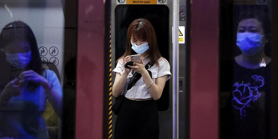 Commuters wearing face masks to protect against the new coronavirus ride in a subway train in Beijing. (Photo   AP)