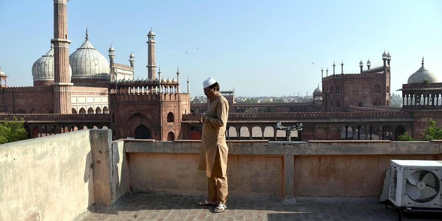 A man offers Namaz on Eid on a rooftop in front of Jama Masjid in Delhi. (Photo  ANI)